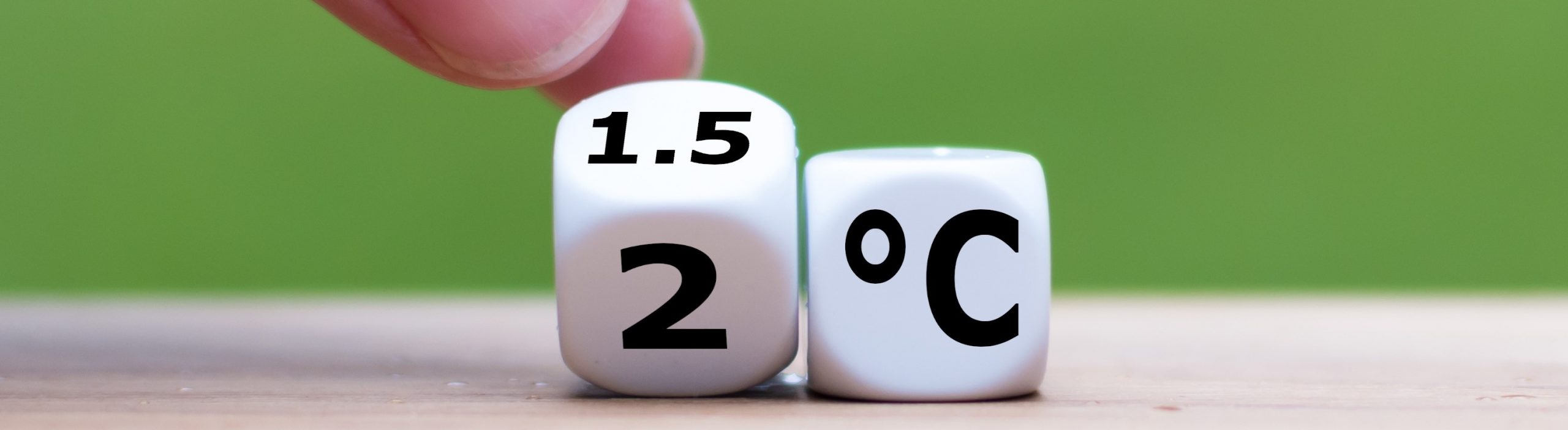 """Symbol for limiting global warming. Hand turns a dice and changes the expression """"2°C"""" to """"1.5°C"""", or vice versa."""