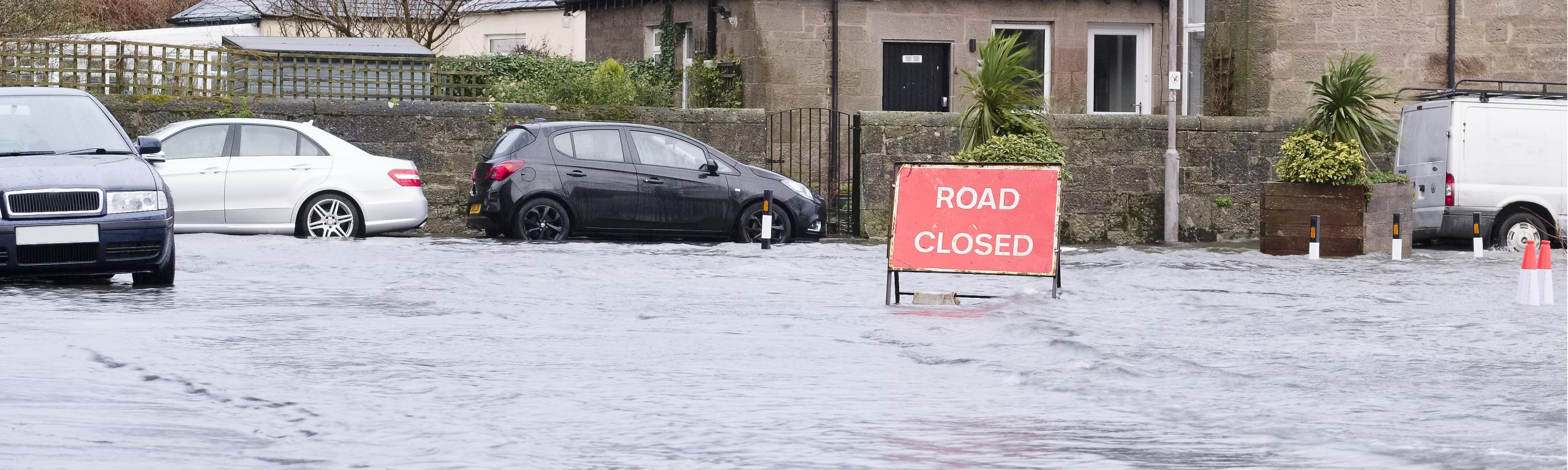 Road flood closed sign under deep water during bad extreme heavy rain storm weather UK