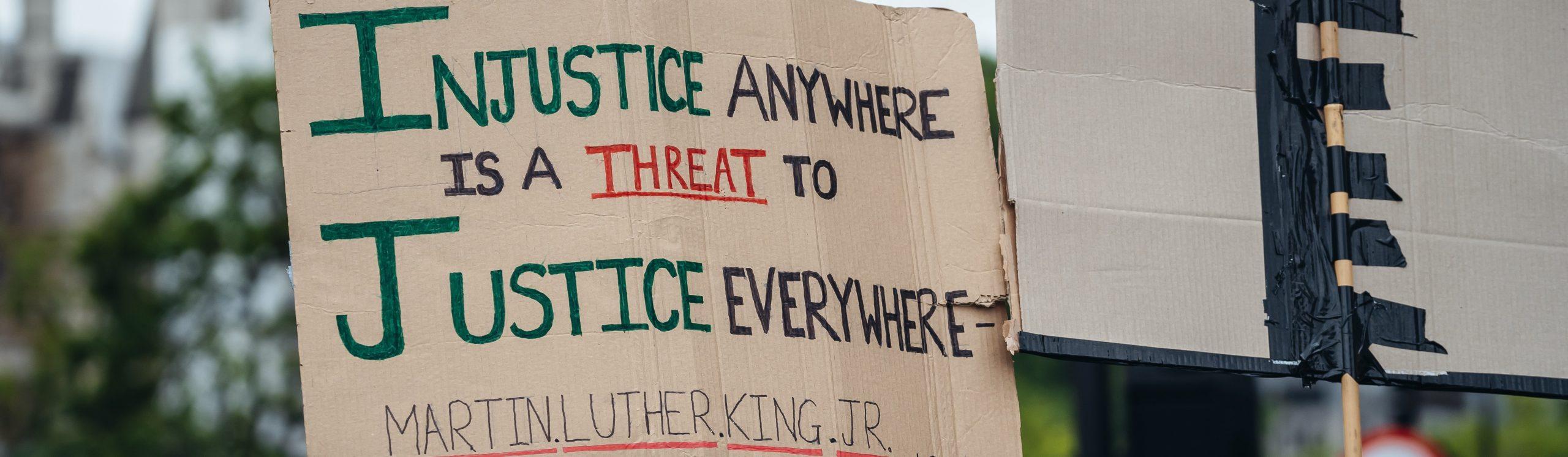 London / UK - 06/06/2020: Black Lives Matter protest during lockdown coronavirus pandemic. Injustice Justice sign