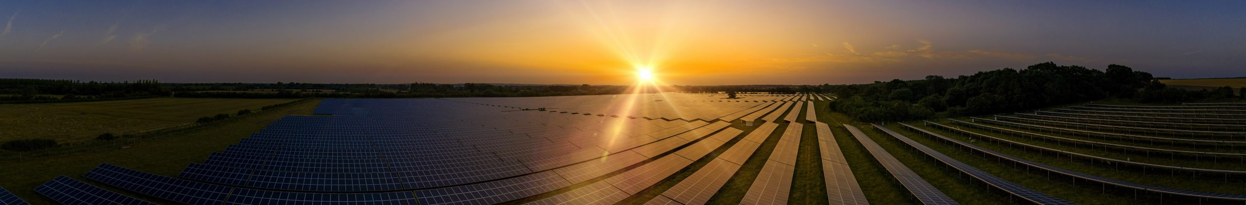 Modern solar farm panoramic at sunrise on a summers day